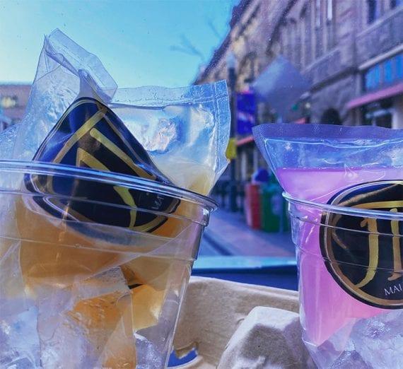 Un sachet de Mai Tai et de vrille d'eau de rose posé dans la glace sur le tableau de bord d'une voiture.