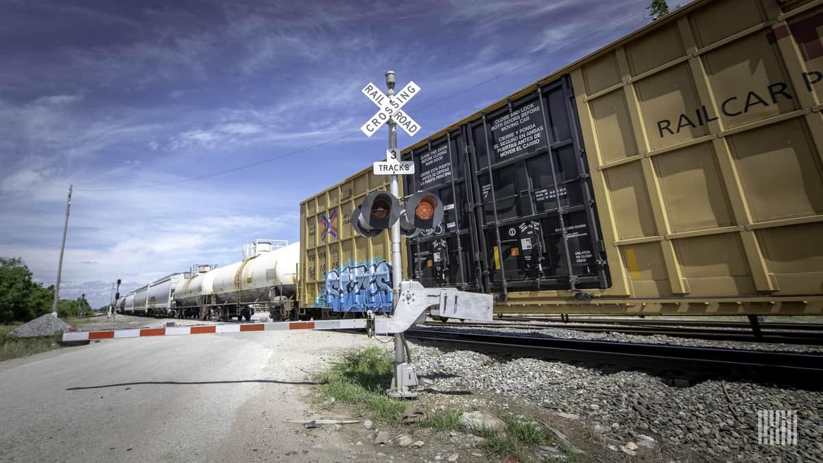 Une photographie de wagons couverts et de wagons-citernes à un passage à niveau.