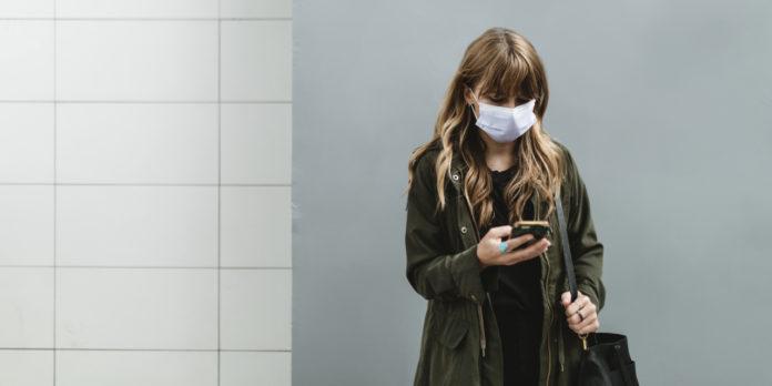 Femme portant un masque facial en public pendant une pandémie de coronavirus