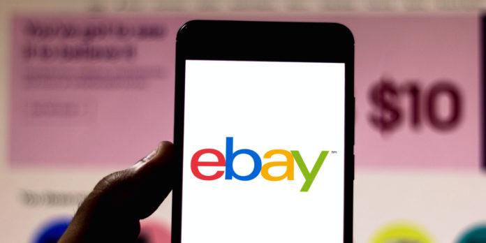 Logo eBay sur le smartphone avec le site web eBay sur le bureau en arrière-plan