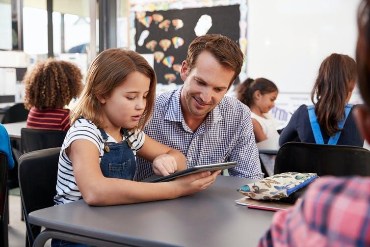 Enseignant et fille regardant la tablette informatique.