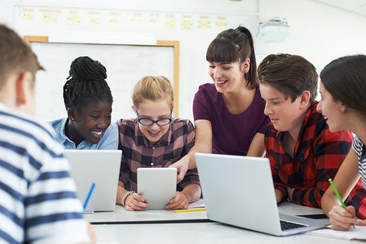 Enseignant et adolescents utilisant des tablettes et des ordinateurs portables.