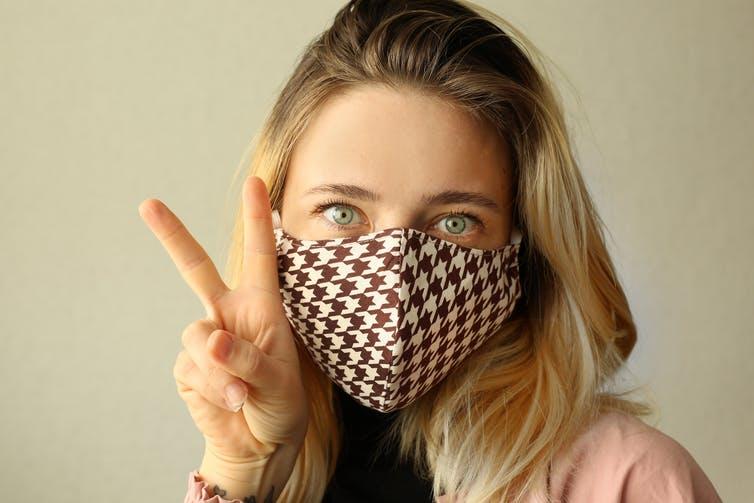 Une femme portant un masque en tissu réutilisable à carreaux.