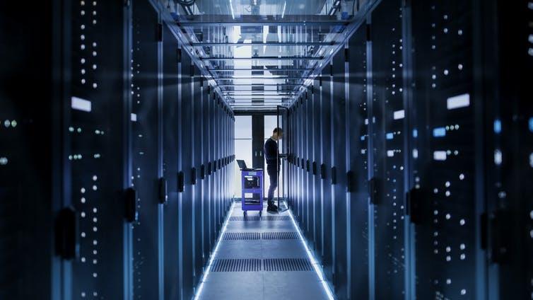 Un homme se tient au bout d'une longue pièce bleuâtre avec des murs de technologie de chaque côté.