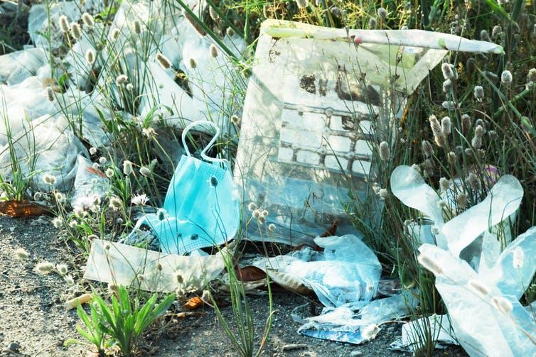 Déchets plastiques jetés dans une zone herbeuse, y compris gants en plastique et masques faciaux.