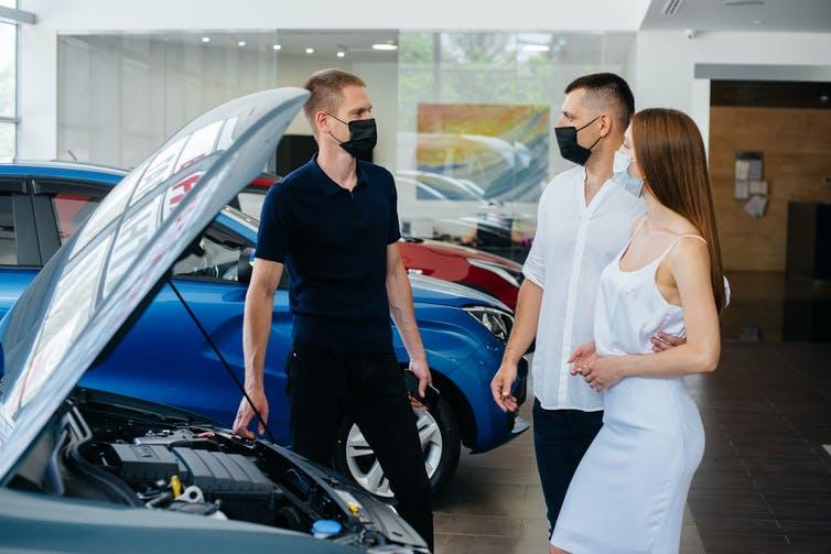 Jeune couple masqué parle à un vendeur devant une voiture.