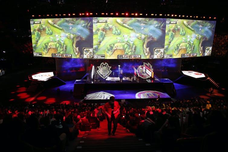 Une arène pleine de gens qui regardent un tournoi international de jeux vidéo